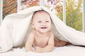 Cheerful Baby Under Blanket In Bedroom