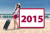 Hispanic Woman With Number 2015 On Beach