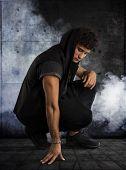 Handsome Young Man Kneeling Down In Dark Hoodie On Black Background