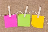 Colorful Sticky Notes With Clothespins On Burlap Background.