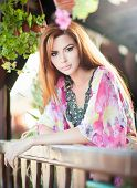 Beautiful female portrait with long red hair outdoor. Genuine natural redhead