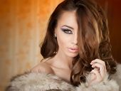 Attractive sexy young woman wearing a fur coat posing provocatively indoor. Portrait of sexy female