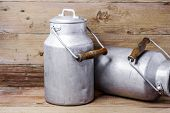 Aluminum old milk cans on a wooden background