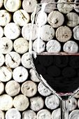 Close-up vertical format image of wine glass on wine corks background