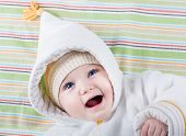 Beautiful Little Baby With Big Blue Eyes Wearing A Warm Hat And A White Winter Jacket On A Colorful