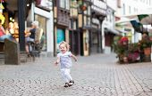 Little Baby Girl Running In A Beautiful Street Of A Historical City Center In Germany