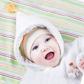 Cute Funny Laughing Baby Girl On Colorful Blanket Wearing A Warm Hat And A White Winter Jacket