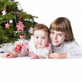 Christmas Portrait Of Little Boy And His Adorable Baby Sister Under A Decorated Christmas Tree