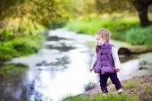 Beautiful Little Baby Girl Walking On A River Shore On A Nice Autumn Day