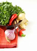 Asian food ingredients (ginger, chilli, coriander and garlic) in traditional utensils