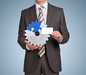 Businessman hold empty card and gear consisting of puzzles