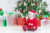 Cute Little Toddler Girl In Santa Hat And Red Dress Playing With A Bell Under A Beautiful Christmas