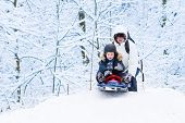 Little Boy Sledding Down A Hill With His Father Helping Him In A Snowy Park