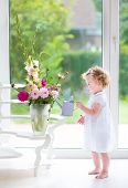 Adorable curly baby girl in a white dress watering flowers in a beautiful living room