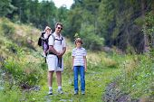 Happy Young Family, Active Father, His Son And A Baby Daughter Hiking Together In The Woods