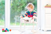 Adorable Toddler Girl With Curly Hair Wearing A Colorful Knitted Dress Reading A Book