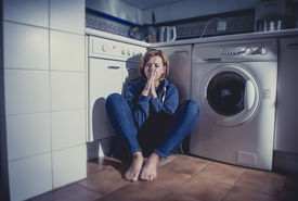 stock photo of barefoot  - lonely depressed and sick woman sitting alone on kitchen floor in stress depression and sadness feeling miserable in barefoot looking desperate - JPG