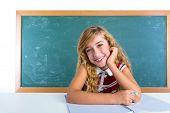 Happy student expression schoolgirl in classroom desk at school green chalk board