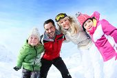 pic of family ski vacation  - Cheerful family of 4 enjoying winter vacation - JPG