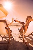 Couple on the beach clinking their glasses while relaxing on their deck chairs
