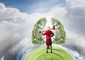 Blond woman in red coat with axe and green tree