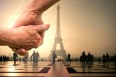 Elderly couple holding hands against eiffel tower