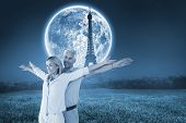 Happy couple standing with arms outstretched against large moon over paris