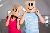 Young couple with bags over heads against white room with open door