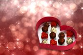 Heart shaped box of candy against shimmering light design on red