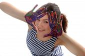 Woman Looks Out Her Hands Painted In Colorful Paint