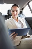 Pretty businesswoman using her tablet pc in her car