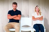 Young couple sitting in chairs not talking during argument against wooden planks