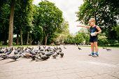 Boy feeding pigeons birds in park