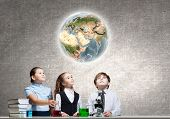 Three cute children at chemistry lesson making experiments. Elements of this image are furnished by NASA