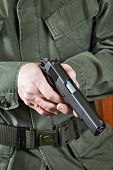 stock photo of colt  - Soldier in uniform holding a gun Colt - JPG