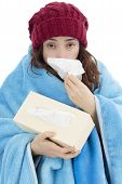 foto of shivering  - SIck flu woman feeling cold and sneezing with a tissue covered with a blanket - JPG