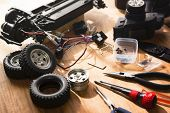 Building model cars. Radio control car assembly scene, RC car assembly on wooden work desk and tools. Natural lighting.