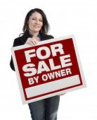 Hispanic Woman Holding For Sale By Owner Real Estate Sign Isolated On White.