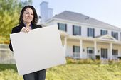 Smiling Hispanic Female Holding Blank Sign In Front of Beautiful House.