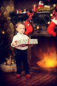 Cute little boy celebrating Christmas at home near the Christmas tree. X-mas decoration. Magic of the Christmas.