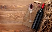 Red wine bottle, wine glass and corkscrew on wooden table background with copy space