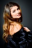 Close-up portrait of a magnificent young woman wearing fur jacket. Studio shot. Beauty, fashion. Make-up, cosmetics.