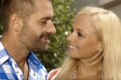 Happy couple having a romantic moment outdoors. Attractive blonde, smiling woman and stubbly handsome man.