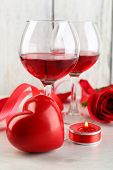 Composition with red wine in glass, red roses and decorative heart on color wooden background