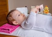 foto of diaper change  - Adorable baby lying playing with a children comb after the change of diaper - JPG