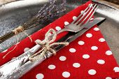 Silverware tied with rope on metal tray with colorful napkin and dried flower on wooden background, macro