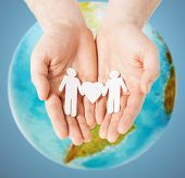 homosexuality, people, love and tolerance concept - close up of male hands holding gay couple paper men with heart shape over earth globe and blue background