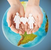 homosexuality, people, love and tolerance concept - close up of female hands holding female gay couple paper figures with heart shape over earth globe and blue background