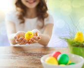easter, holiday and child concept - close up of girl holding yellow chicken toy and bowl of colored eggs on table over lights background