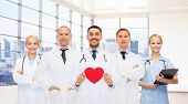 medicine, cardiology, healthcare and people concept - happy young doctors cardiologists with red heart over clinic background